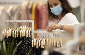 ep archivo - mujer con mascarilla en una tienda de ropa