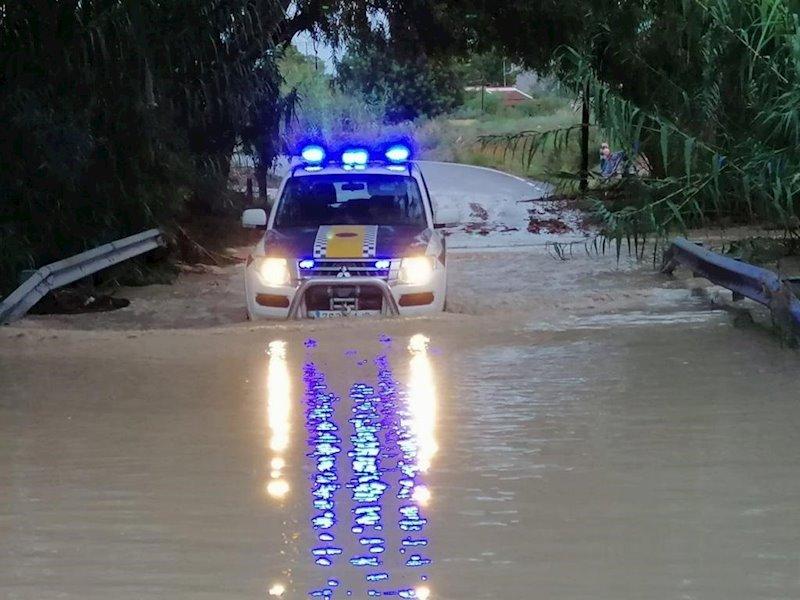 ep coche de la policia local de alicante en un camino anegado por la lluvia