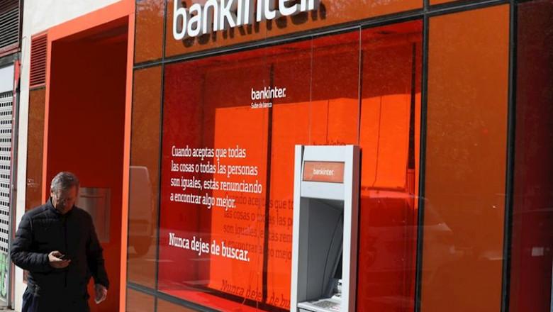 ep un hombre pasa al lado de un cajero del banco bankinter